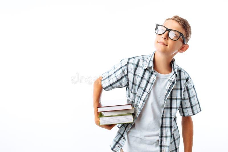 拿着堆书的美丽的学生,植物学家去与书在白色背景的演播室学习 库存照片
