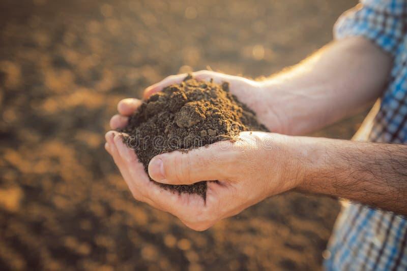 拿着堆可耕的土壤的农夫在手上 免版税库存照片