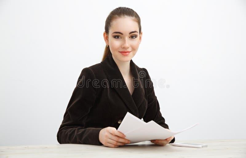 拿着堆文件的黑暗的夹克的女孩 免版税库存图片
