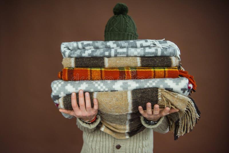 拿着堆毯子的人 图库摄影