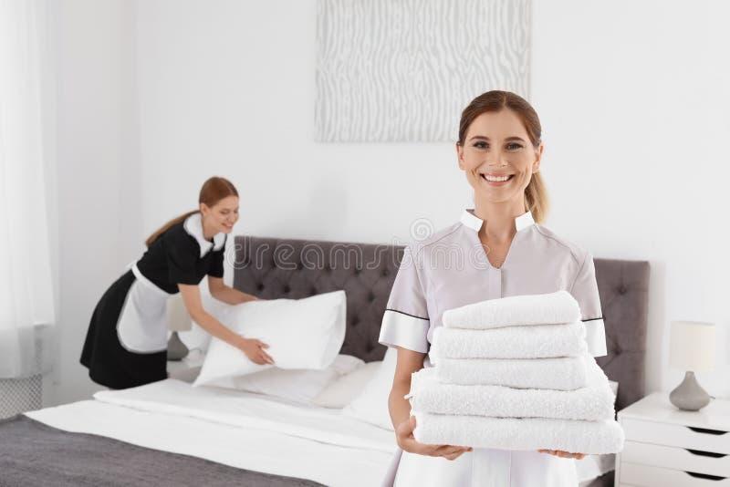 拿着堆清洁毛巾的专业女服务生在卧室 库存图片