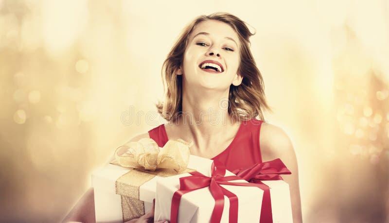 拿着堆礼物盒的少妇 免版税库存图片