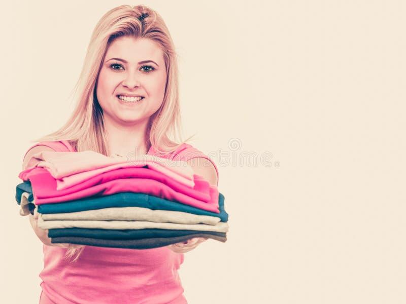 拿着堆被折叠的衣裳的妇女 免版税库存图片