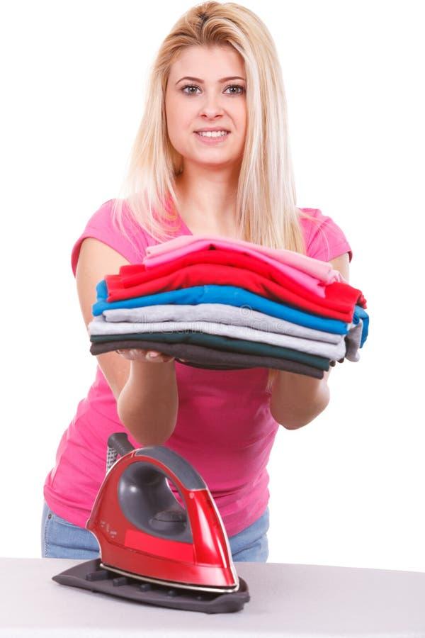 拿着堆被折叠的衣裳的妇女 免版税库存照片
