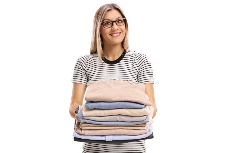 拿着堆被电烙的和被包装的衣裳的少妇 免版税库存照片