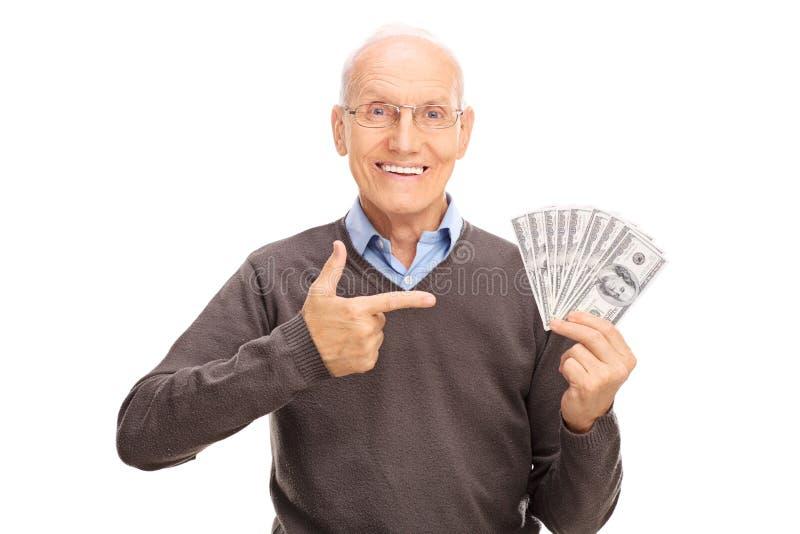拿着堆金钱的高兴前辈 免版税图库摄影