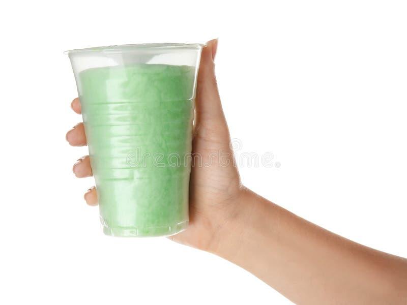 拿着塑料杯子用在白色背景的美味的棉花糖的妇女 免版税库存图片