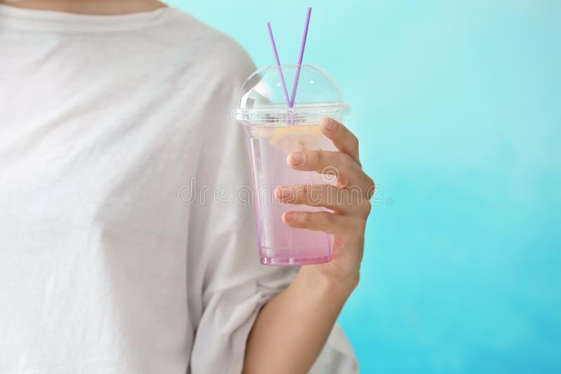 拿着塑料杯子用在颜色背景,特写镜头的新鲜的淡紫色柠檬水的妇女 免版税库存图片