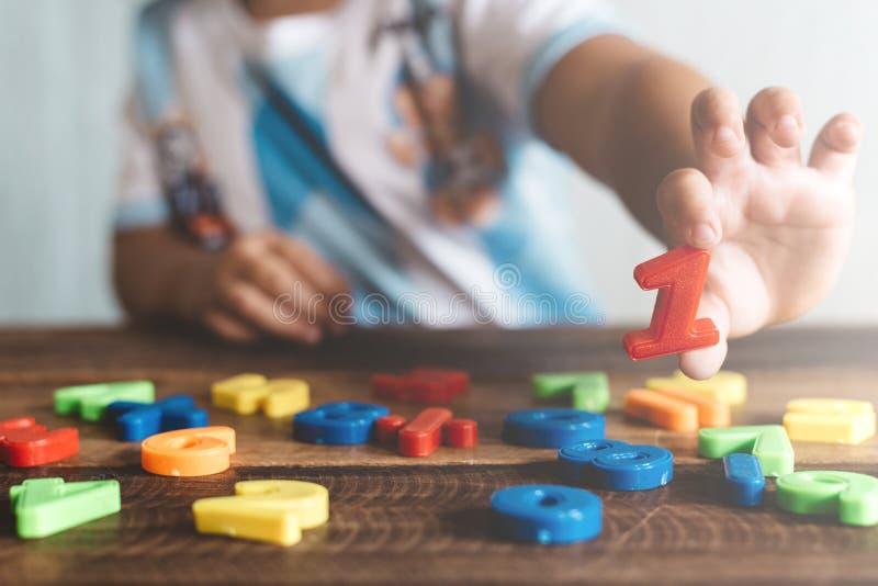 拿着塑料玩具第一的孩子,她学会计数 库存图片