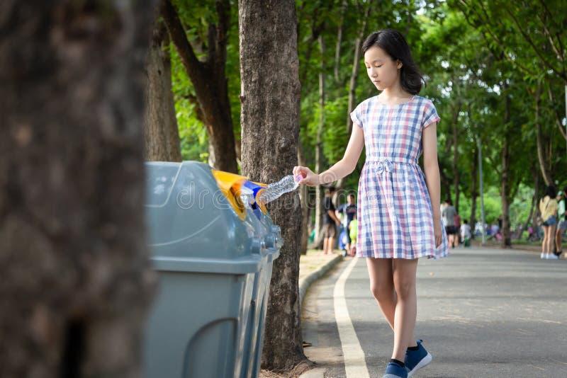 拿着塑料瓶的亚洲小孩女孩手,投入塑料水瓶在回收站,旅游妇女手投掷 免版税库存照片