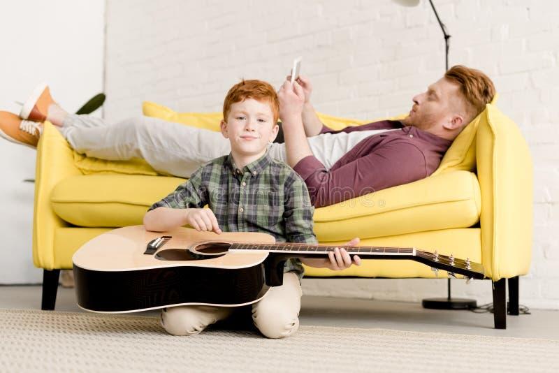 拿着声学吉他广告的逗人喜爱的小男孩微笑对照相机,当父亲使用数字片剂时 库存照片