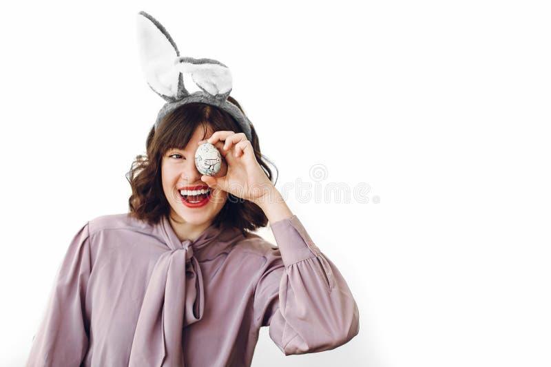 拿着复活节彩蛋和smil的兔宝宝耳朵的美丽的时髦的女孩 库存图片