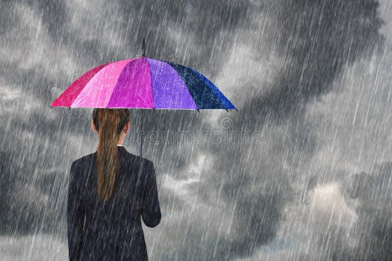 拿着多彩多姿的伞的女商人在与秋天的天空下 免版税库存照片