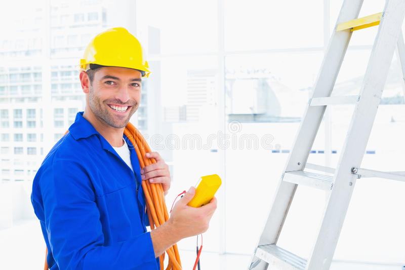 拿着多用电表的微笑的男性电工在办公室 免版税库存照片