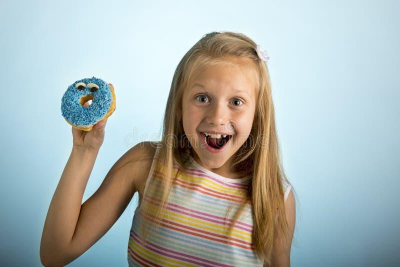 拿着多福饼的年轻美好的愉快和激动的白肤金发的女孩8或9岁在看起来她的手上离开痉挛和快乐在sug 库存图片