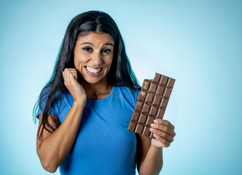 拿着大可口巧克力片剂的便服的美丽的年轻逗人喜爱和愉快的拉丁妇女看与诱惑 库存照片