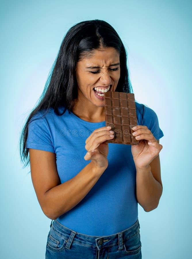 拿着大可口巧克力片剂的便服的美丽的年轻逗人喜爱和愉快的拉丁妇女看与诱惑 免版税库存图片