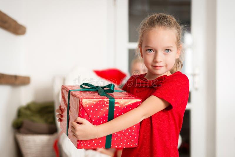 拿着大圣诞礼物,微笑和看照相机的逗人喜爱的激动的少女 在圣诞节的愉快的孩子 库存照片