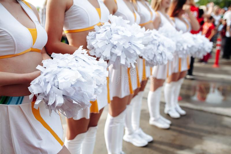 拿着大型机关炮的白色制服的啦啦队员 关闭 橄榄球冠军 免版税库存图片