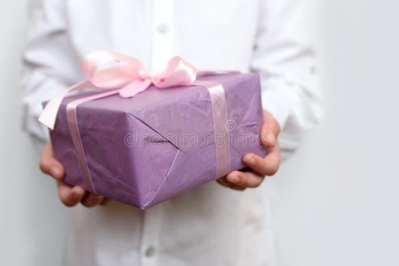 拿着大紫色当前箱子的孩子被包裹在桃红色丝带在手上 情人节、母亲节或者生日庆祝概念 库存图片