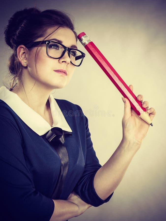 拿着大过大的铅笔的妇女考虑某事 库存图片