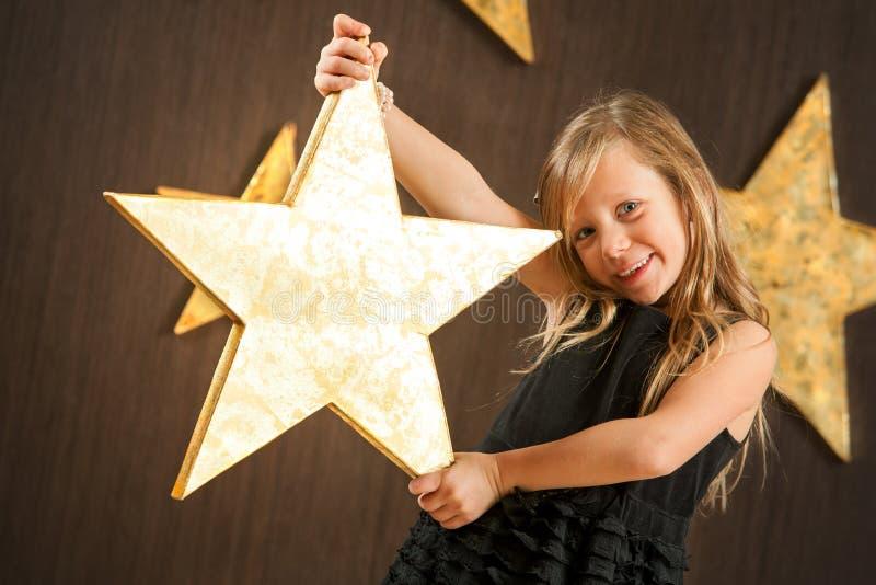 拿着大金黄星形的逗人喜爱的女孩。 库存图片