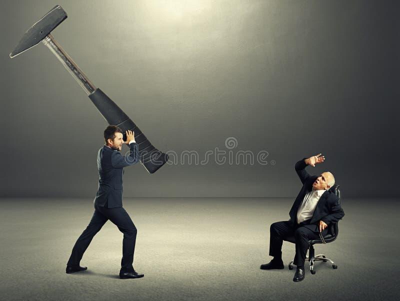 拿着大锤子的被注重的年轻商人 免版税图库摄影