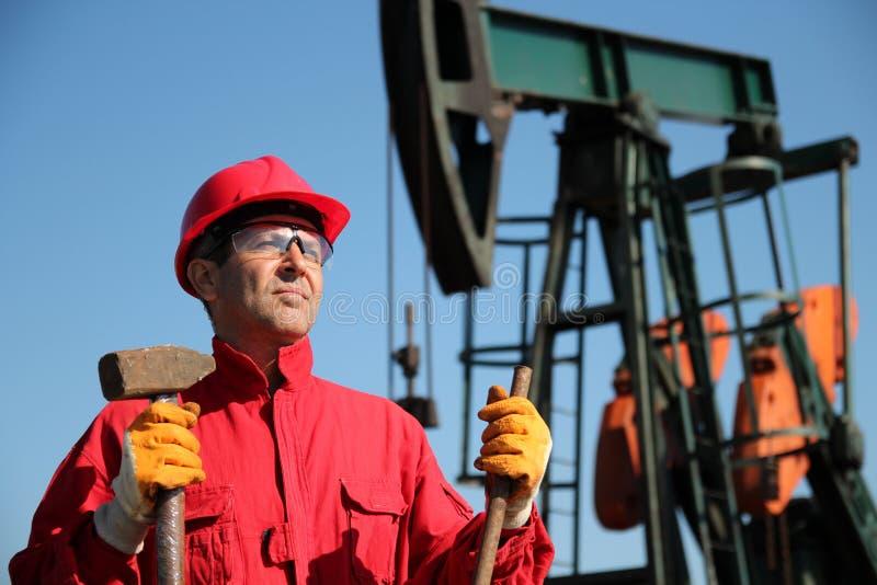拿着大锤的石油工业工作者在泵浦杰克旁边。 免版税库存图片