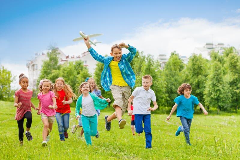 拿着大飞机的跳的男孩戏弄和孩子 免版税库存照片