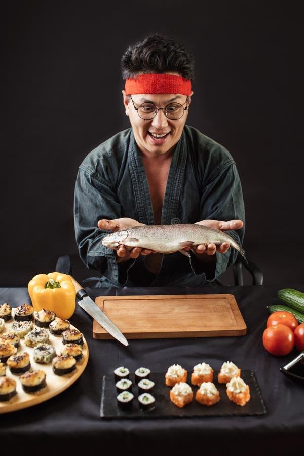拿着大鱼的情感惊奇的人在厨房屋子 库存图片