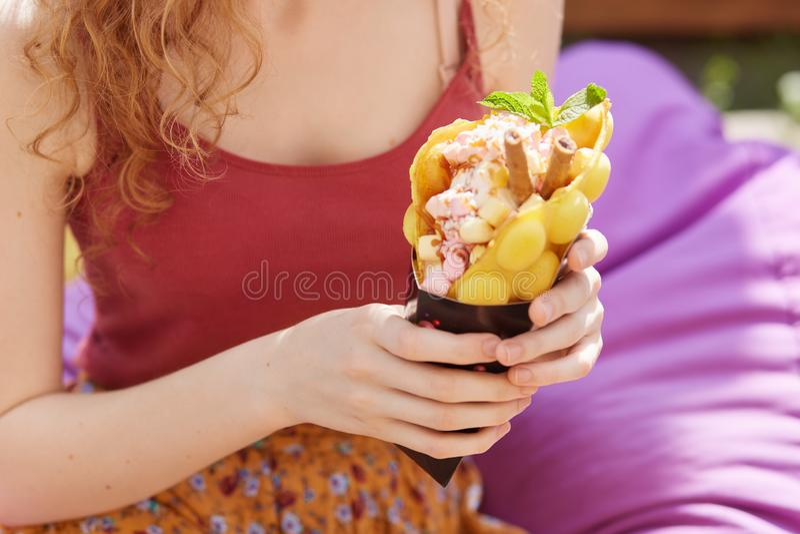 拿着大黄色冰淇淋的未知的妇女画象,当坐紫色frameless椅子,隔绝在城市公园背景,时 免版税图库摄影