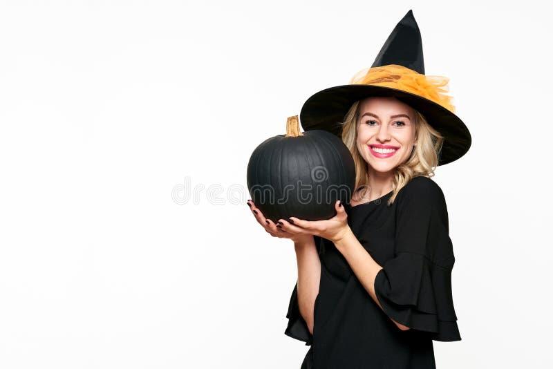 拿着大黑南瓜的华美的微笑的万圣夜巫婆 一个美丽的少妇佩带的巫婆帽子的画象 万圣节 免版税库存图片