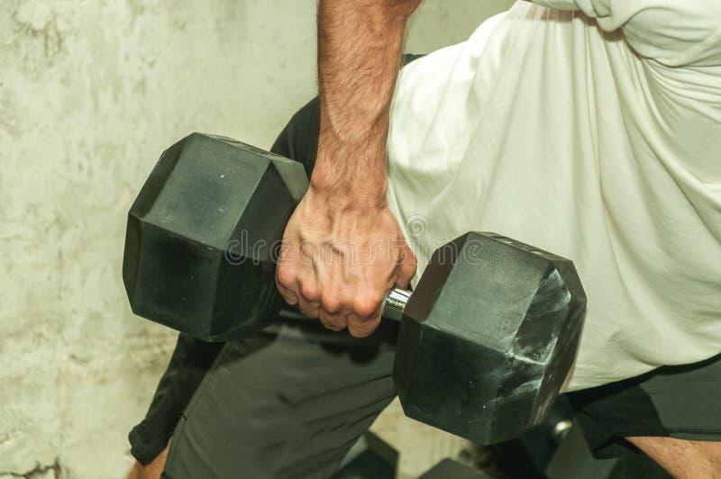 拿着大黑大量的哑铃重量的一个坚强的肌肉人的手作为背部肌肉的锻炼在健身房 免版税库存图片