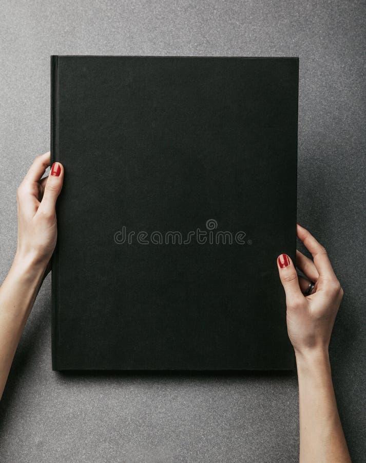拿着大黑名册的女性手 垂直 免版税库存图片