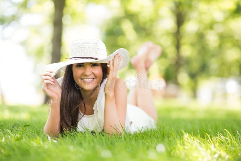拿着太阳帽子的愉快的妇女,当说谎在草原时 免版税库存图片