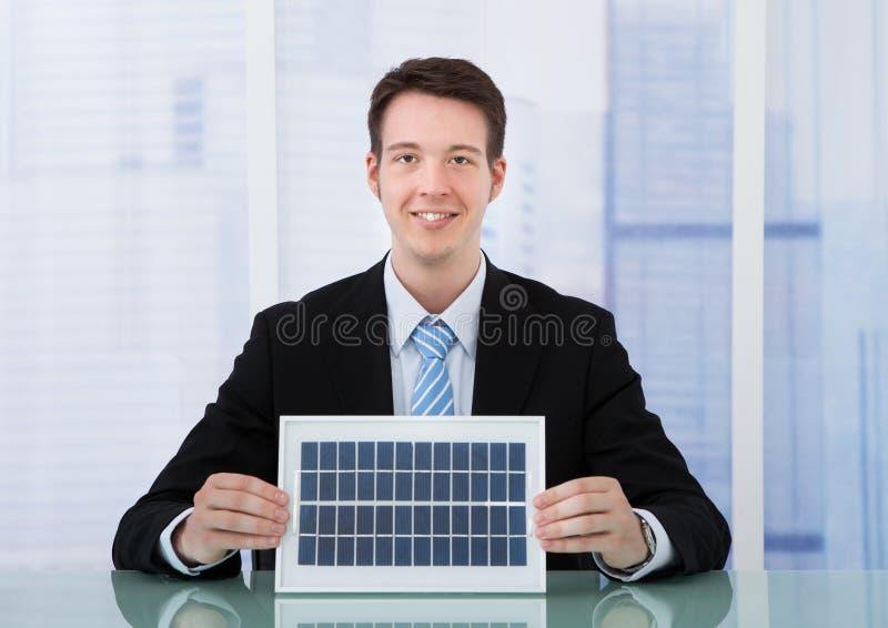 拿着太阳电池板的确信的商人在书桌 图库摄影