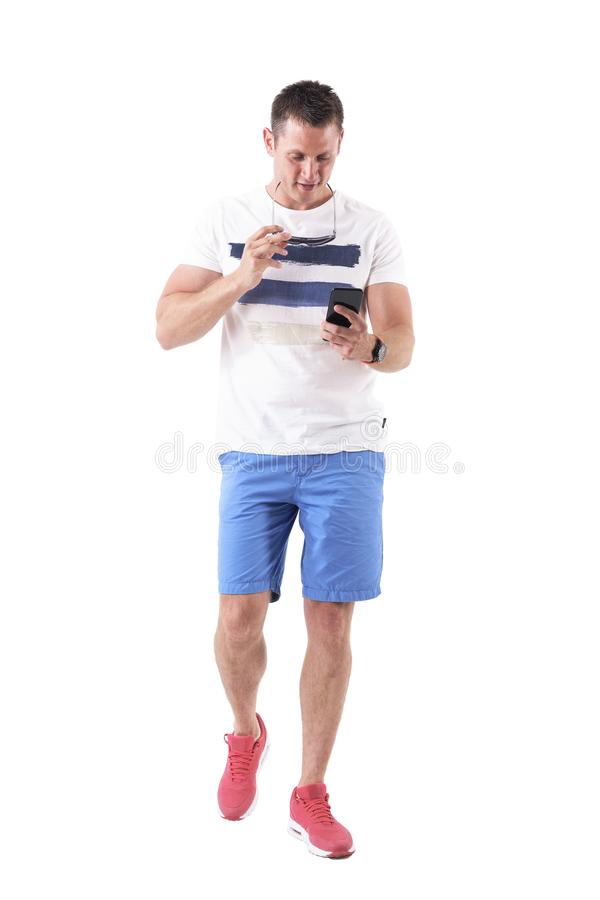 拿着太阳镜的凉快的帅哥走和使用智能手机 库存图片