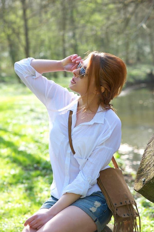 拿着太阳镜的美丽的少妇户外 免版税库存照片