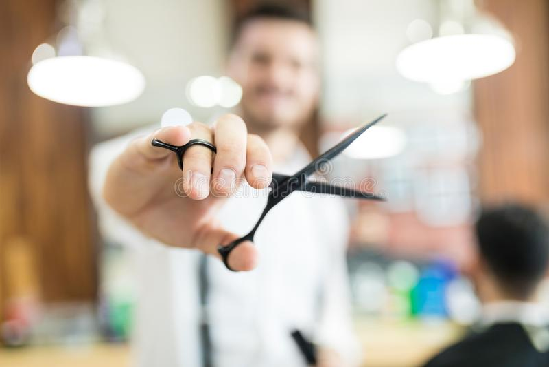 拿着头发切口剪的美发师,当工作在商店时 免版税库存照片
