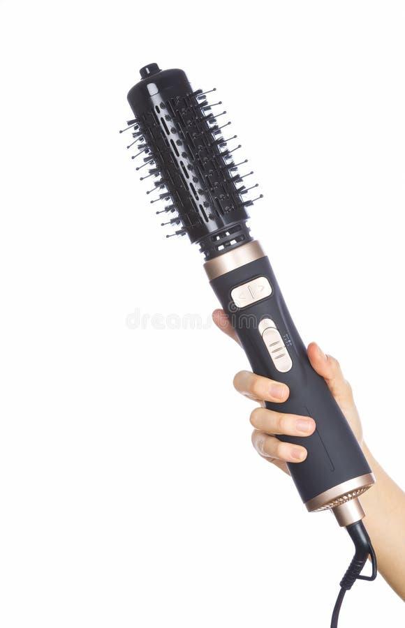 拿着头发烫发钳回合刷子的手 库存图片