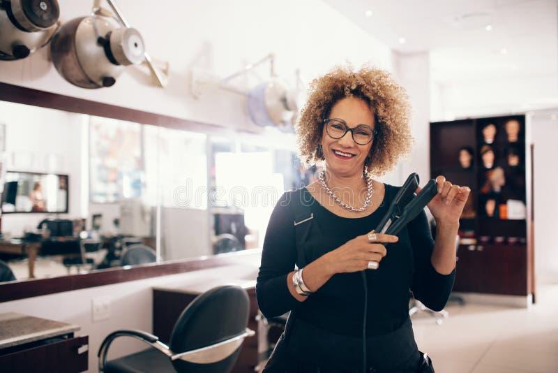 拿着头发直挺器的沙龙的女性美发师 免版税库存照片