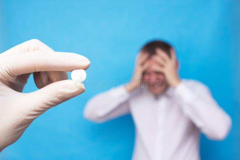拿着头疼的以有头疼的一个人为背景,头疼的概念药片,止痛药的医生一个药片 库存照片