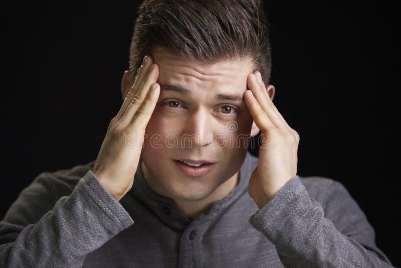 拿着头的一名担心的年轻白人的画象 免版税库存照片