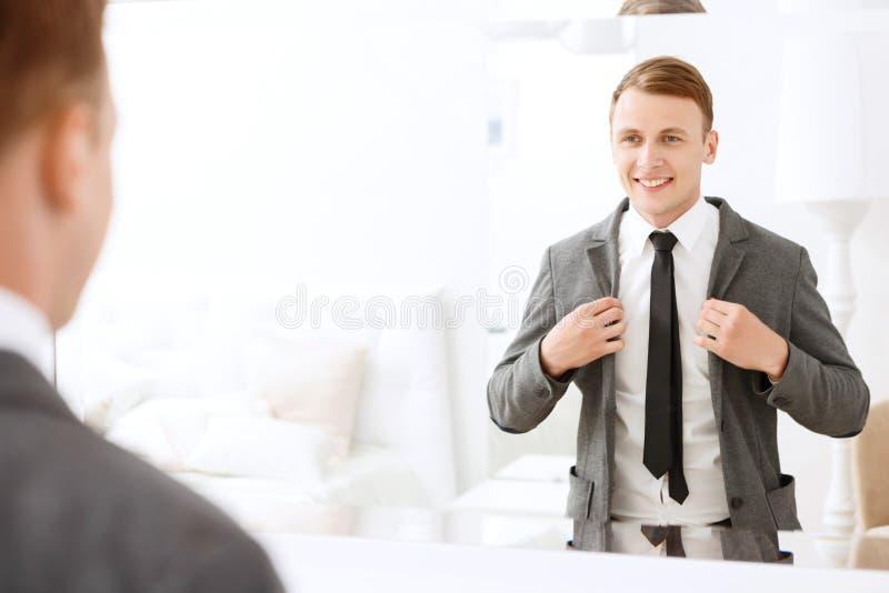 拿着夹克的微笑的人把放在他上 免版税库存照片