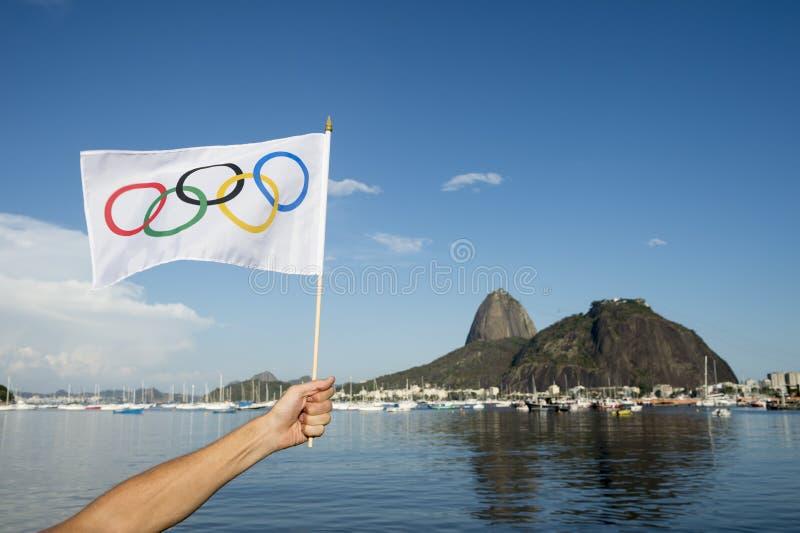 拿着奥林匹克旗子里约热内卢的手 库存图片