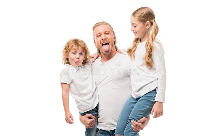 拿着女儿和儿子在手上的鬼脸人画象 库存照片