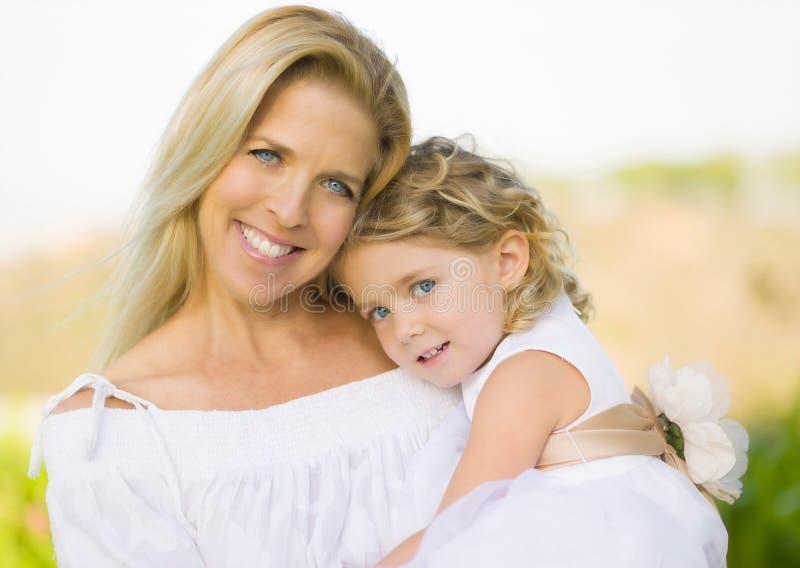 拿着女儿女花童的母亲 库存照片