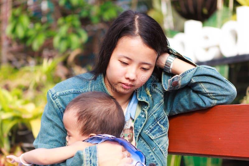 拿着女儿的母亲坐在公园 免版税库存照片