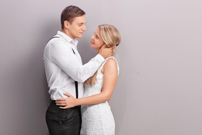 拿着女孩的典雅的人亲吻她 库存图片