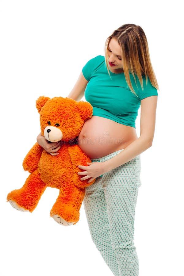拿着女用连杉衬裤的孕妇涉及她的腹部,在白色背景 免版税库存图片